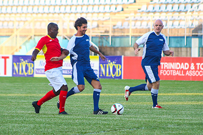 Pablo Aimar, centre, comes under challengefrom T&T's legend Russell Latapy with FIFA President Gianni Infantino providing support during Monday's Goodwill football match at the Ato Boldon Stadium in Couva. Photo by Nicholas Williams.