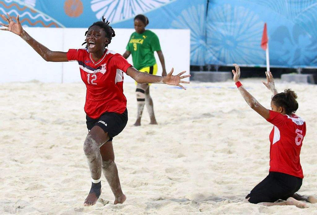 GOLDEN GIRLS: Trinidad and Tobago's J'Nae Harris, left, races to join her celebrating teammates as another T&T player gives thanks, at the final whistle in the Youth Commonwealth Games Girl's Beach Soccer gold medal match against Jamaica in Nassau, Bahamas on Saturday. —Photo: AFP