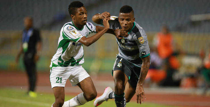 Santos's Andres Renteria tries to ward off DirecTV W Connection's Shannon Gomez (white jersey) during their Scotiabank CONCACAF Champions League game on September 22, 2015, in Port of Spain, Trinidad & Tobago. (Photo: Allan V. Crane)