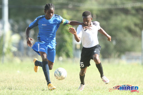 Photo: The Uprising Youths captain (left) tries to hold off a Crown Trace FC attacker during the 2015 Republic Bank National Youth Cup quarterfinals. ....(Courtesy Allan V Crane/Wired868)