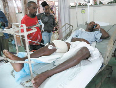 National senior footballer Keron Cummings speaks on his cell phone while warded at the Port-of-Spain General Hospital after being shot in the leg after returning home from a party on Saturday. Cummings was expected to join the national team in camp ahead of the Copa America Centenario match against Haiti on January 8. Photo: MARCUS GONZALES