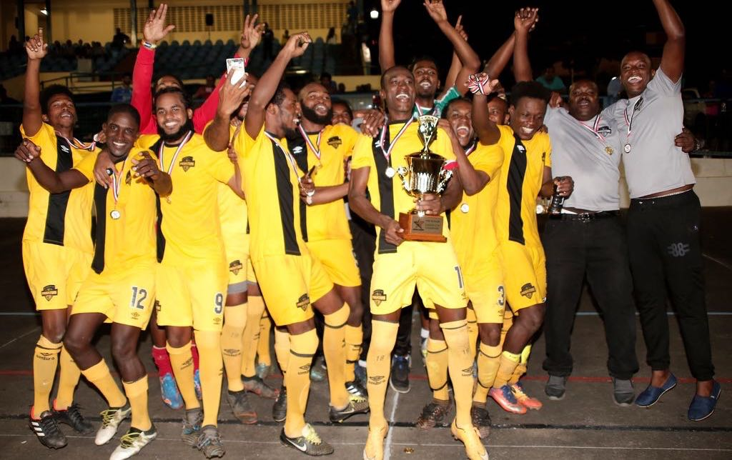 Members of Cunupia FC celebrate after winning the T&T Super League Cup final against rival Queen's Park Cricket Club at the Arima Municipal Stadium on Sunday night.
