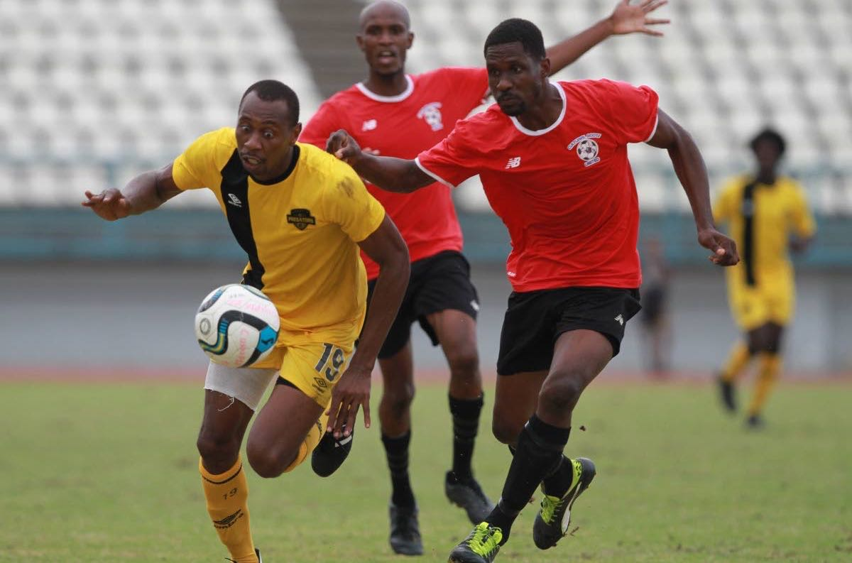 Cunupia FC striker Kevon Woodley, left, on the attack against Club Sando at the Larry Gomes Stadium, Arima, recently.