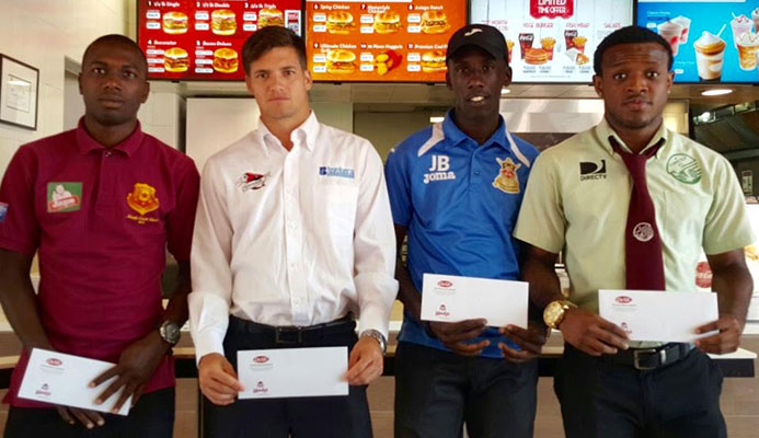 Left to right: North East Stars' Keron Cummings, Central FC's Sean De Silva, Defence Force's Jerwyn Balthazar and W Connection's Jomal Williams display their Wendy's Player of the Month vouchers on Feb. 22 at Wendy's Ariapita Avenue restaurant in Woodbrook, Port of Spain.