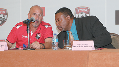 T&T's Senior Men's football team head coach, Stephen Hart, left, and TTFA president David John Williams share a few words during yesterday's unveiling of the TTFA's newest sponsor, SCG (Caribbean) Group Limited at Hyatt Regency, Port-of-Spain. Photo: MARCUS GONZALES