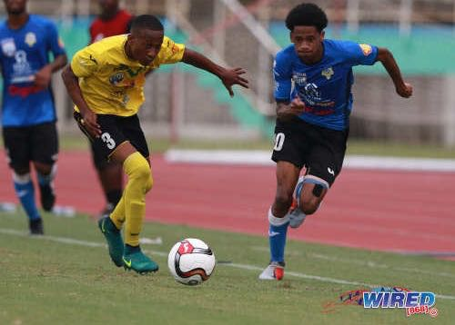 Photo: Presentation College (San F'do) winger Jordan Riley (right) tries to escape from St Benedict's College defender Merlik Campbell during SSFL action in Marabella on 26 September 2018. (Copyright Nicholas Bhajan/CA-Images/Wired868)