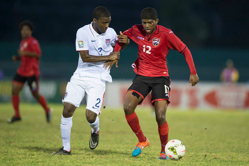 Photo: Trinidad and Tobago winger Kishun Seecharan (right) is kept in grip by United States right back Shaquell Moore. Moore is the child of Trinidad and Tobago immigrants to the United States. ...(Courtesy CONCACAF)