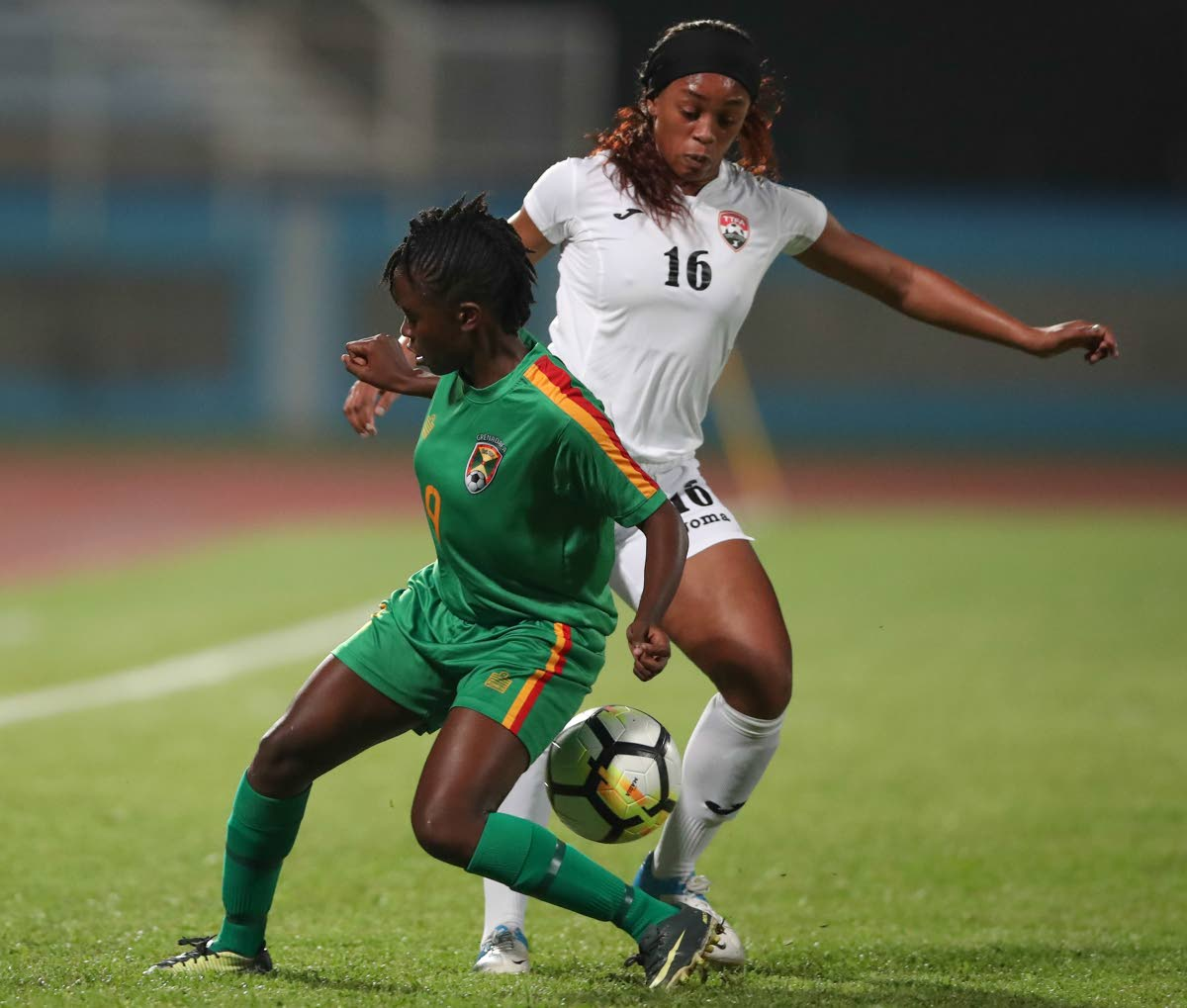 Trinidad and Tobago's Linda Hinds, right, battles Grenada's Sheranda Charles in the CFU Women's Challenge Series 2018 at the Ato Boldon Stadium, Couva, recently.