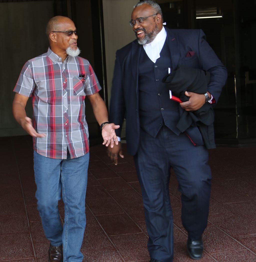 T&T Super League president, Keith Look Loy, left, with his attorney Matthew Gayle leaves Hall of Justice in Port-of-Spain after winning his case against the T&T Football Association (TTFA), yesterday.