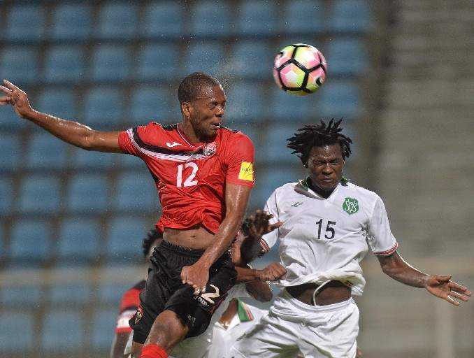 Trinidad and Tobago's Carlyle Mitchell, left, rises above Suriname's Miquel Darson while contesting a header during action from last night's clash, in the Caribbean 5th-place qualifying series for a berth in this year's CONCACAF Gold Cup, at the Ato Boldon Stadium in Couva. Suriname won the match 2-1 in extra time. —Photo: DEXTER PHILIP