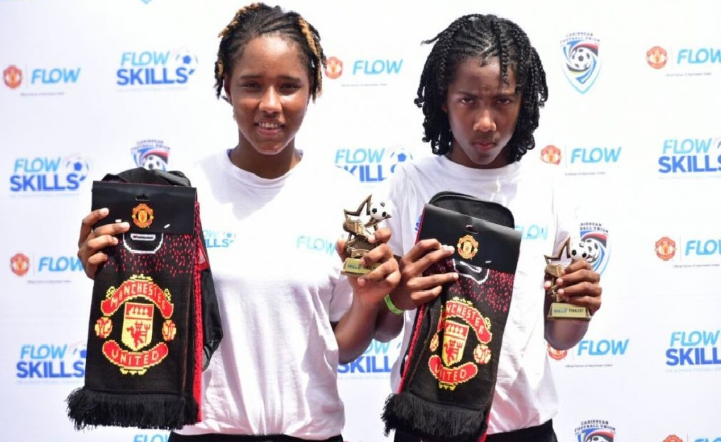 Winners: Female footballer, Moenesa Mejias (left) and 13-year-old, Molik Khan (right), pose with their Flow and ManU tokens at the Ato Boldon Stadium, Couva, yesterday.