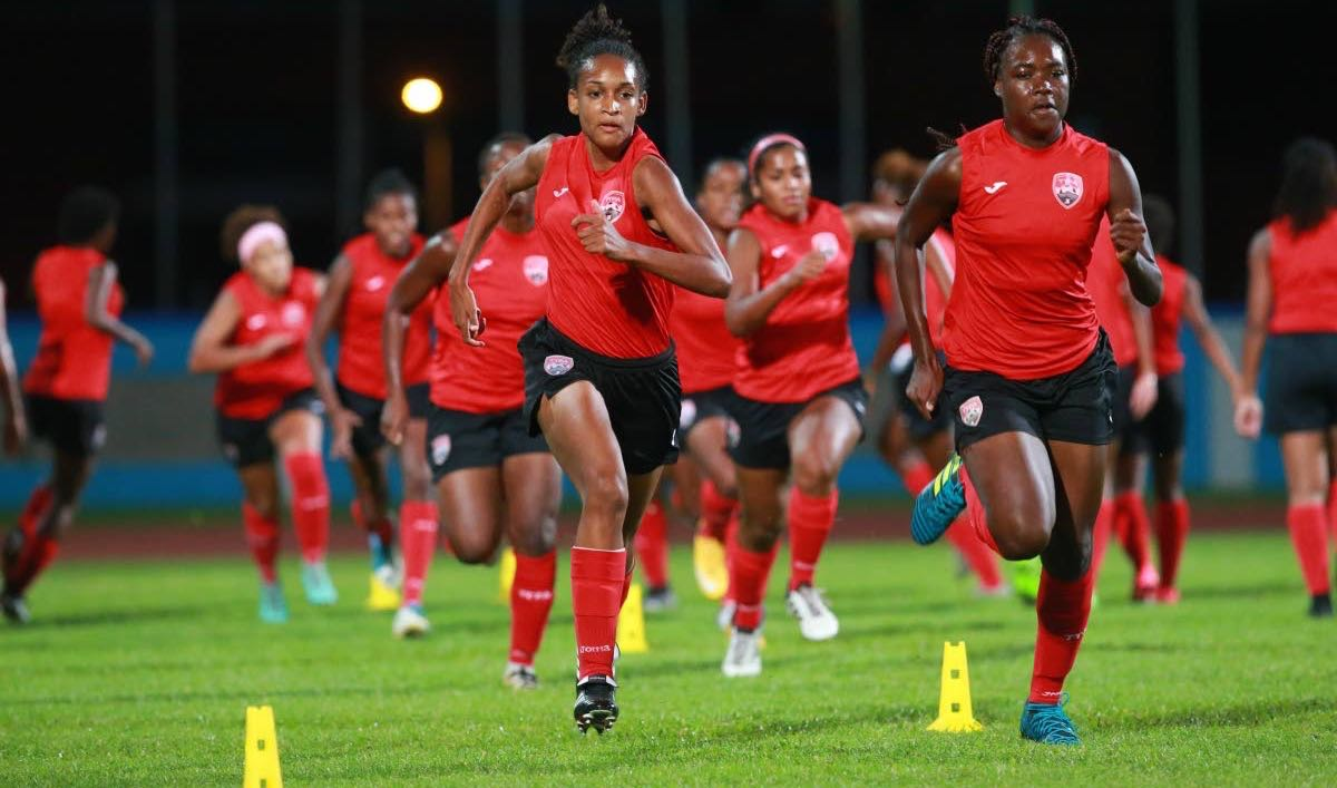 TT's Under-20 players Brittney Williams (front left) and Natisha John (front right) sprint in a warm-up exercise on Sunday at the Ato Boldon Stadium, Couva.