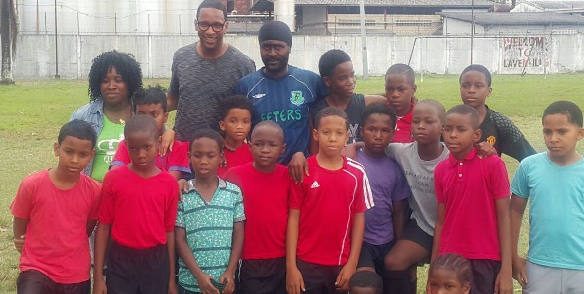 Former national player Shaka Hislop (second left, back row) poses with T&T Maestors players and their coach Sheldon DeFreitas (back centre) as well as youth football organiser Nekeisha (back left).