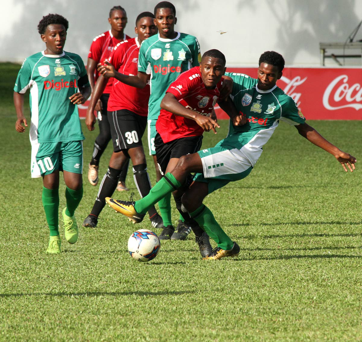 St Anthony's Romario Burke, second from right, is tackled as he makes a run against Trinity College in the Coca Cola North Zone Intercol final yesterday at CIC Ground, St Clair.