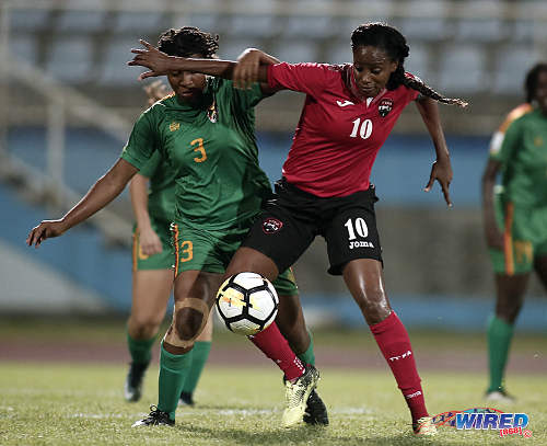 Photo: Trinidad and Tobago captain Tasha St Louis (right) holds off Grenada defender Treasher Valcin during 2019 World Cup qualifying action at the Ato Boldon Stadium on 27 May 2018. (Copyright Chevaughn Christopher/Wired868)