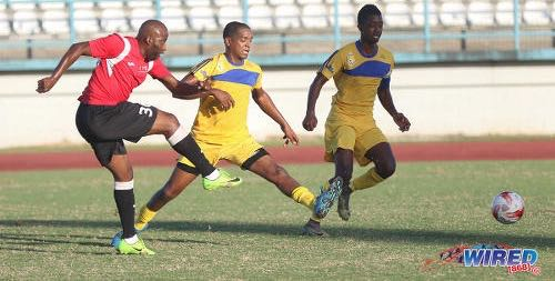 Photo: UTT striker Cornell Glen (left) fires home the decisive goal past FC Santa Rosa defenders Jesse Reyes (centre) and Alfie James during TTSL action at the Larry Gomes Stadium on 10 December 2017. ...(Courtesy Sean Morrison/Wired868)
