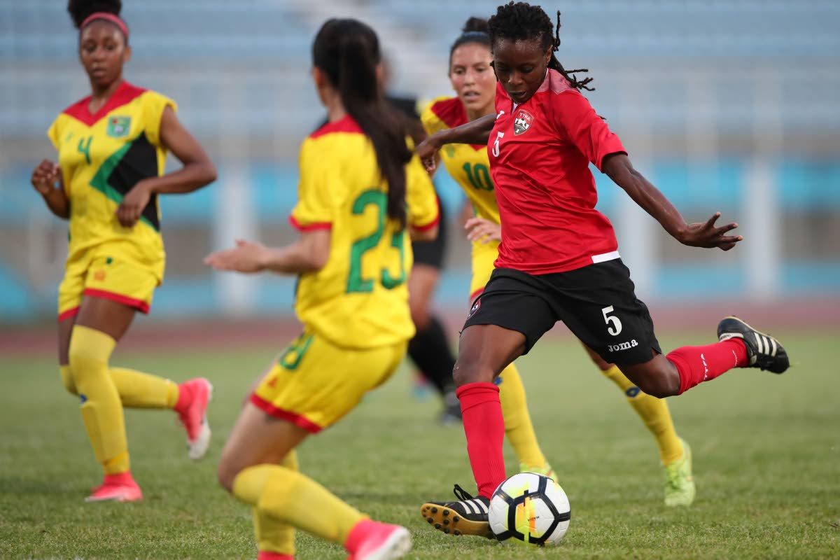 T&T's Jenelle Cunningham (#5) has a shot on goal between Guyana defenders Nailah Rowe (#4) Rylee Traicoff (#23) and Mariam El-Masri (#10), during the CFU Women's Challenger Series 2018 between TT (red) and Guyana (yellow) at the Ato Boldon Stadium, Couva, yesterday.