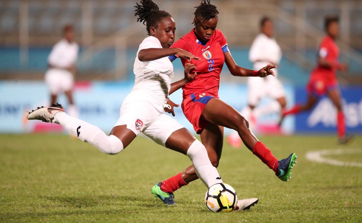 Haitian defender heads the ball away from TT midfielder Shenieka Paul during the two Caribbean nations' opening match in the 2018 CONCACAF U20 Women's Championships at the Ato Boldon Stadium yesterday.