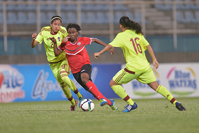 T&T's Ranae Ward,centre, blows past two defenders during the Women's International friendly between T&T and Venezuela at the Ato Boldon Stadium in Couvaon Wednesday.