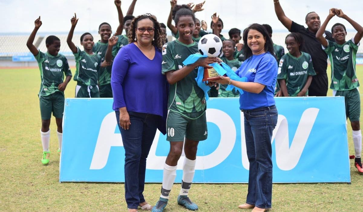 Flow senior marketing manager Ria Maharaj, front right, and TT Pro League CEO Julia Baptiste, front left, present W Connection Under-14 captain Molik Khan, centre, with the Flow Youth Pro League Cup U-14 trophy at Larry Gomes Stadium in Arima on Sunday