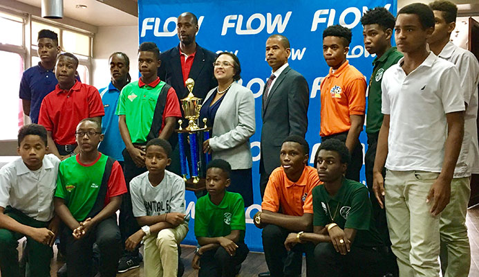 Cindy-Ann Gatt, Director of Marketing at Flow (with trophy), is flanked by Trinidad and Tobago Men's Senior Team head coach Dennis Lawrence (L) and TT Pro League CEO Dexter Skeene, along with Flow Youth Pro League players during the launch of the 2017 Flow YPL at the VIP Lounge of the Hasely Crawford Stadium on 3 March 2017.