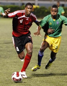 T&T captain, Sheldon Bateau, left, goes past St Vincent and The Grenadines' Nical Stephens in their Caribbean Football Union Under-20 Group D qualifier at the Marvin Lee Stadium, Macoya on Wednesday night. T&T won 4-1. ...Photo: Anthony Harris.