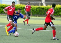 Williams chased: Trinidad & Tobago midfielder Jomas Williams, left, carries the ball under pressure from Cuba's Lezaro Collado. The teams met in a CFU Under-17 Boys qualifying tournament for the 2011 FIFA Under-17 World Cup yesterday at the Marvin Lee Stadium, Macoya. —Photo: Stephen Doobay.