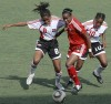 U-17 players, Victoria Swift (left) and Jo-Marie Lewis, try to take the ball away from senior team winger, Tasha St Louis (centre) during a clash between the two national sides at the Marvin Lee Stadium, Macoya last Wednesday. The senior women won the match 2-1. Photo: Anthony Harris