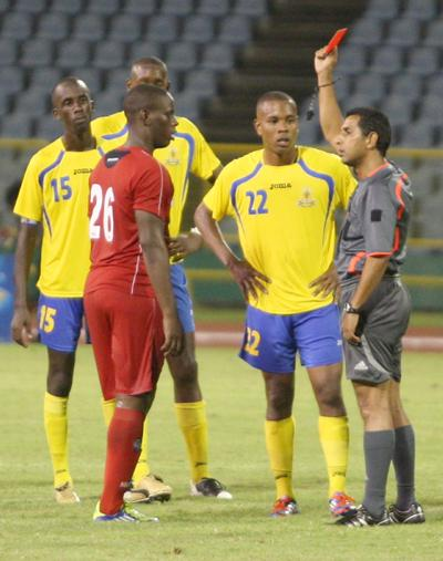 Referee Michael Ragoonath, right, issues red cards to Neal & Massy Caledonia AIA's Devorn Jorsling, left, and Curtis Gonzales of Defence Force during the Lucozade Sport Goal Shield final at the Hasely Crawford Stadium, Mucurapo last month. Caledonia won 3-1. Photo: Anthonty Harris.