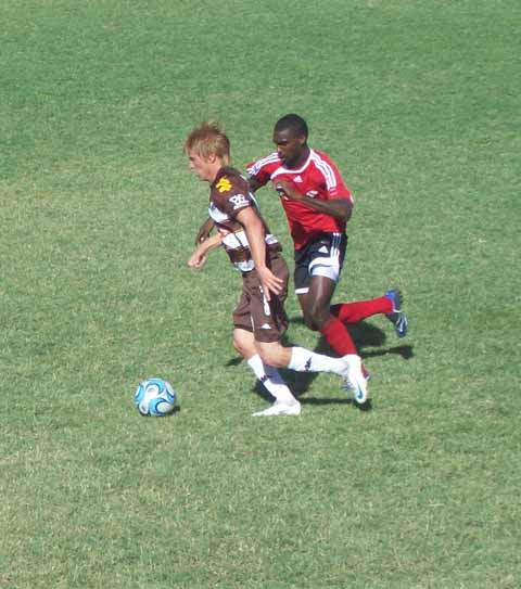 From right: Atlentico Platense midfielder Braian Robert being marked by T&T's Clyde Leon.