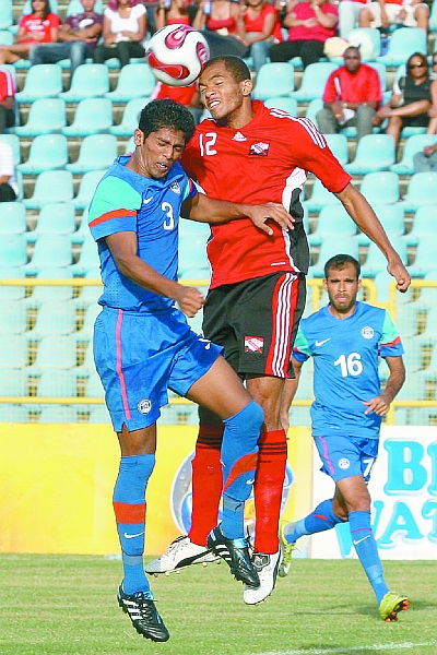 India's Raju Gaikwad (3) and T&T's Darryl Roberts in an aerial battle during yesterday's friendly international at the Hasely Crawford Stadium. Roberts scored a double as T&T won 3-0. (PHOTO: TT Guardian).