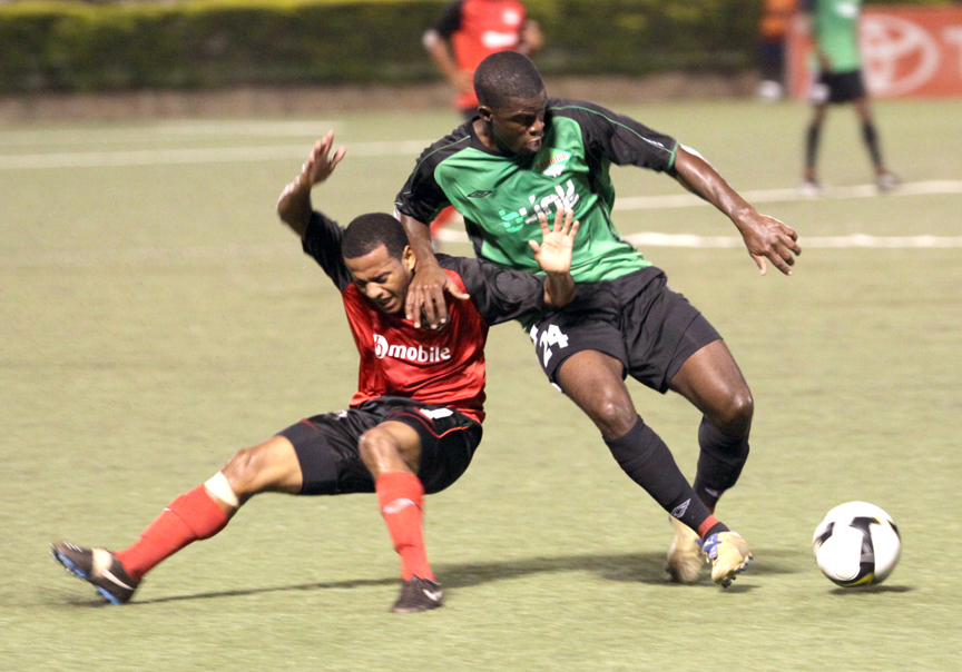 Public attacker Hayden Tinto is fouled by Jabloteh defender Glenton Wolfe before the Toyota Classic's opening goal. Photo: Kenroy Ambris.