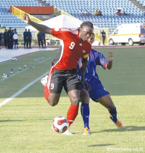 SOCA WARRIORS skipper Kenwyne Jones has a shot to goal under a challenge by Bermuda defender Reginald Thompson Lambe. Jones scored the only goal of the match. ...Author: ROGER JACOB
