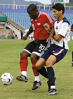 Russell Latapy of T&T collects cleanly and screens off Dominican Republic's defender Francisco Torres during the first half of play in the warm-up match yesterday at Hasely Crawford Stadium in Mucurapo. T&T won 9-0. ...Photo: Anthony Harris (T&T Guardian)