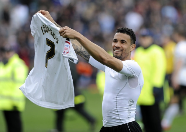 Ipswich Town skipper Carlos Edwards waves his shirt at the away fans following the 2012/13 season finale at Burnley.
