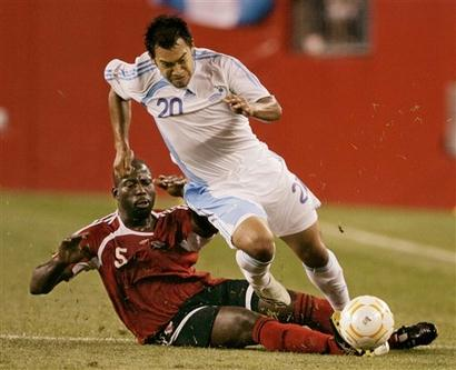 Hard knocking Keyeno Thomas slides in on Carlos Ruiz of Guatemala.