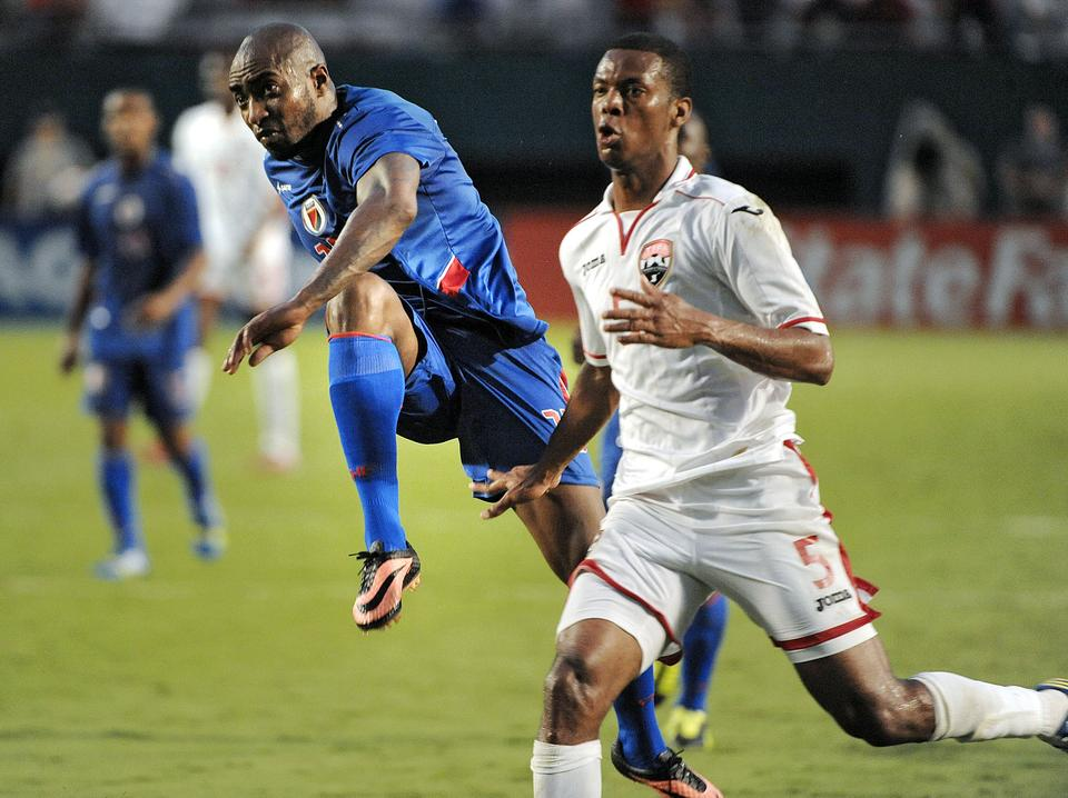 Haiti's Yves Hadley Desmaret takes a shot in front of Trinidad and Tobago's Carlyle Mitchell during the second half of their game, Friday, July 12, 2013, at Sun Life Stadium.