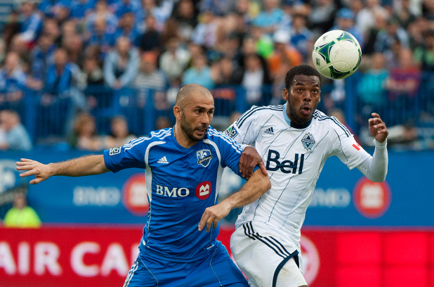 Vancouver Whitecaps centre back Carlyle Mitchell, right, battles for the ball against Montreal Impact's Marco Di Vaio, left, during an MLS regular season game on Sept. 21. 2013