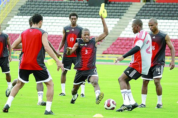 Kern Cupid number three and Glenroy Samuel go for the ball, while team-mates Carlos Edwards, Under-20 forward Juma Clarence # 19 and Julius James # 16 look on during the Soca Warriors practice session at the Hasely Crawford Stadium. Photo: Anthony Harris