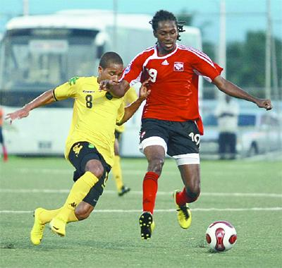 Jamaica's defender Eric Verna, left, attempts a sliding challenge on T&T's Keon Daniel during yesterday's friendly match at the Marvin Lee Stadium, Macoya. Jamaica won 3-1. Photo: ANTHONY HARRIS