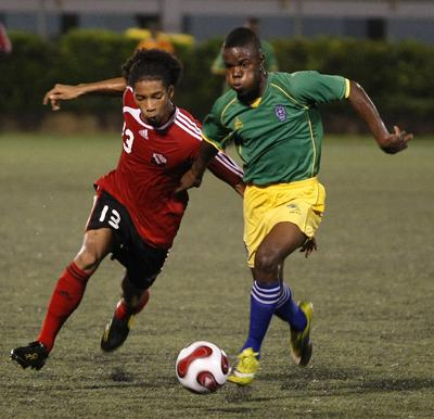 T&T's Dion Mc Cree attempts to get elude St Vincent and The Grenadines' Nical Stephens in their Caribbean Football Union Under-20 Group D qualifier at the Marvin Lee Stadium, Macoya on Wednesday night. T&T won 4-1. Photo: Anthony Harris.