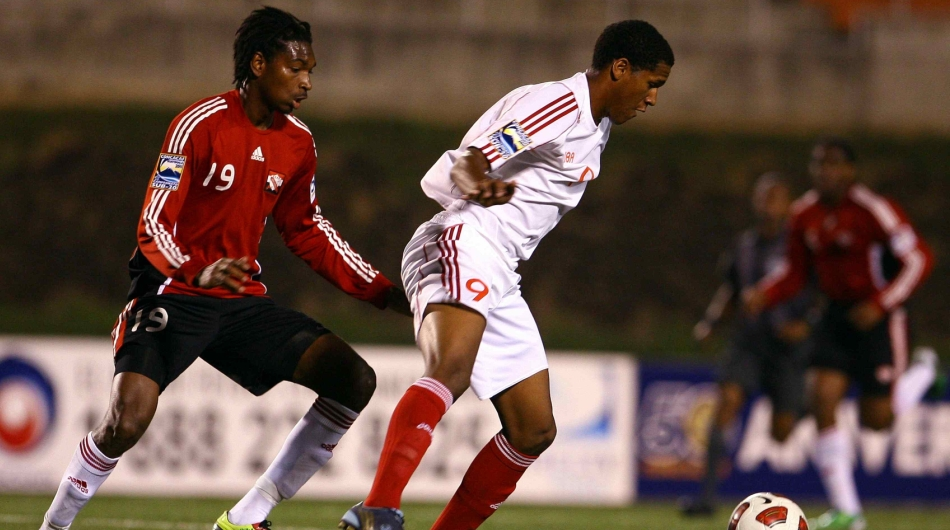 T&T's Weslie John keeps a close eye on Cuban striker Yaudel Lahera.
