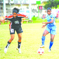 WOLF ACTION: Trincity Nationals player Elisa Olivero, left, and Simeone Connell of Defence Force contest the ball during a Trinidad and Tobago Women's League Football (WOLF) Premier League match at St George's College ground, Barataria last week Friday. Trincity Nationals won 2-0. –Photo: Anisto Alves