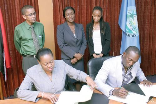 Dwight Yorke, seated right, signs on the dotted line, in the presence of administrator of the Division of Tourism Claire Davidson-Williams, seated left, Secretary of the Division of Tourism Tracy Davidson-Celestine, standing centre, Marketing Officer in the Division, Nigel Wilson, standing left, and Communications Specialist Aisha Sylvester.