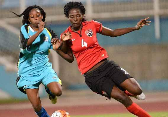 RACE ON: T&T's Daniela Findley, right, vies for possession with St Lucia's Joanne Alphonse during action from Friday night's CFU Olympic qualifier clash at the Ato Boldon Stadium, Couva. T&T shutout their Caribbean rivals 6-0. — Photo: DEXTER PHILIP