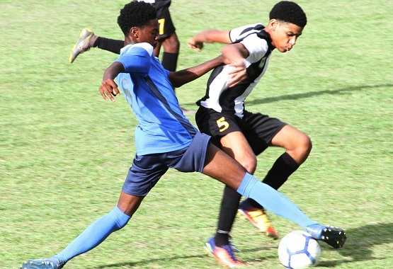 Mikel St. Martin of Holy Cross College(R) wards of a strong tackle for the ball from Dorian Jeffery of Arima North Secondary School,yesterday,during action in the Secondary schools Football League East Zone match at Arima North's grounds.
