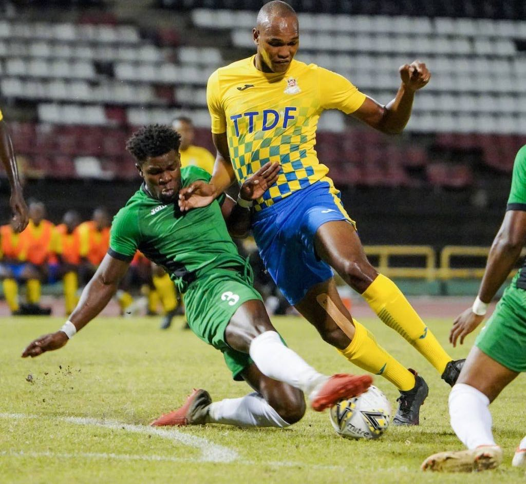 Defence Force FC striker Brent Sam (right) gets a heavy skate tackle from W Connection's Isaiah Garcia (No 3) during the TT Pro League match between Defence Force FC and W Connection FC at the Hasely Crawford Stadium, Port of Spain, on Saturday. - Daniel Prentice/CA-images