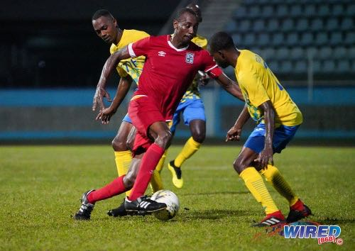 Photo: Cunupia FC attacker Kevon 'Showtime' Woodley (centre) tries to find a way past two Defence Force opponents during Pro League action at the Ato Boldon Stadium on 18 February 2020. (Copyright Daniel Prentice/Wired868)