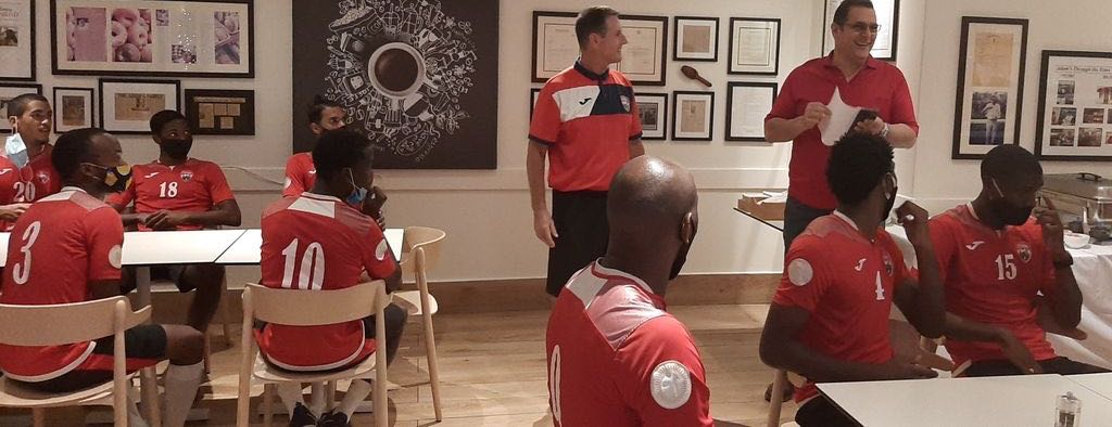 Members of the national training squad listen attentively as restaurant owner Adam Aboud, right, and coach Terry Fenwick address them yesterday at Adam's Gourmet Restaurant and Bakery in Maraval.