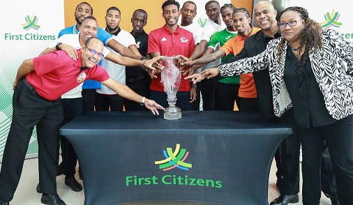Representatives of the 12 T&T Pro League clubs are flanked by Senior Manager Communication and public relations First Citizens Dexter Charles, second from right, and CEO Julia Baptiste, right, put their hands on the champions trophy during the Media Launch of the First Citizens Cup at the Diego Martin Sporting Complex, Bagatelle, Diego Martin, yesterday. ...CA-images